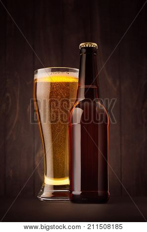 Brown beer bottle and glass weizen with golden lager on dark wood board vertical mock up. Template for advertising design branding identity.