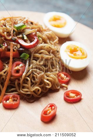 Fried asian instant noodles with boiled egg and vegetables