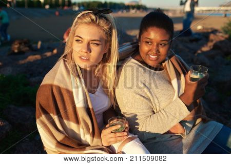 Intercultural girls with drinks admiring sunset on the beach on summer evening