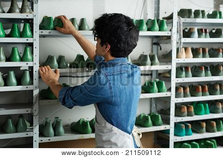 Self-employed cobbler standing in front of shelves with footwear forms and choosing model of shoes for new order