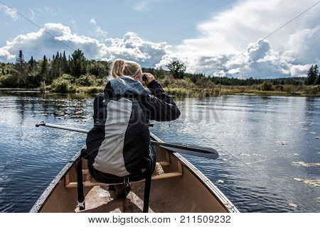 Girl using binocular canoeing with Canoe on the lake of two rivers in the algonquin national park in ontario Canada on a sunny cloudy day