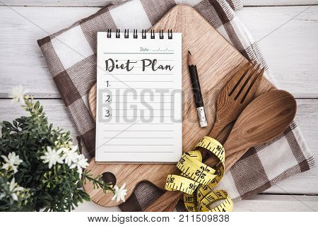 Line Notepad with Diet Plan list text on chopping board with wooden fork and spoon and measuring tape on white table recipes food or diet plan for healthy habits shot note background concept
