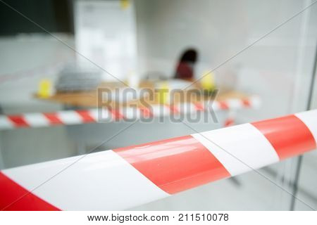 Blurred shot of crime scene: striped crime scene tape, interior of modern office with desk, chair and marker board on background