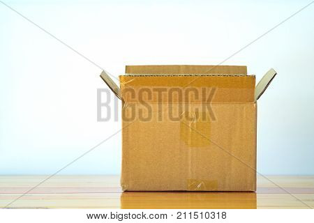 Empty opened old brown cardboard box for mock up on bright wooden table with copy space.
