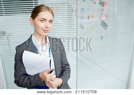 Waist-up portrait of attractive young white collar worker looking at camera with warm smile while standing at corridor of modern office building