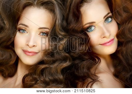 Young beautiful twins women with healthy  skin and luxurious curly updo hair