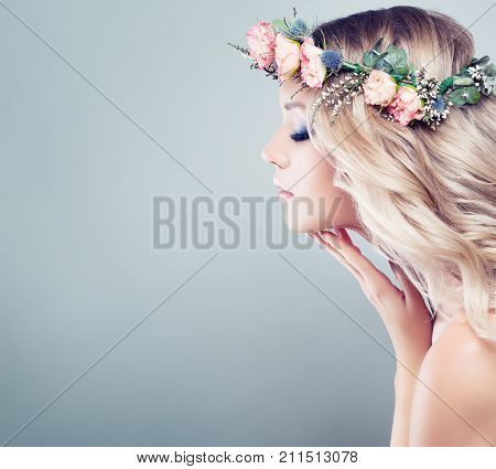 Perfect Young Woman with Spring Flowers. Blonde Beauty. Long Wavy Hair Healthy Skin Fashion Makeup. Beauty Girl with Flowers Hairstyle on Blue Background