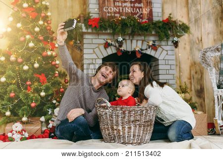 Young Playful Happy Parents With A Cute Little Baby Boy Doing Selfie On Photo Camera In A Decorated