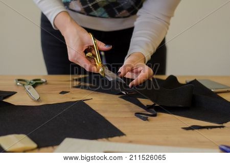 seamstress at work on the table, tailor woman work in studio with clothes