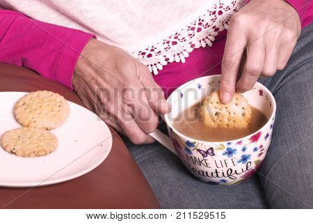 Dunking fruit biscuits in a hot cup of tea
