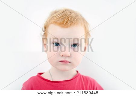 The redhead child just awake on the white background
