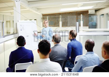 Mature confident teacher pointing at whiteboard during presentation in front of audience