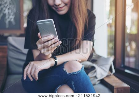 Closeup image of a beautiful Asian woman holding and using at smart phone sitting cross leg in modern cafe