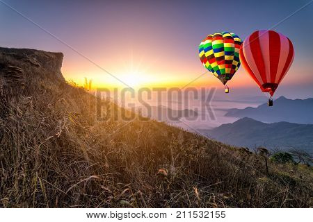Hot air balloon with tourist is traveling into the peak of mountain and cloudscape at Phu chi fa in Chiangrai Provice Thailand. woman traveler standing looking beautiful hot air balloon and mist at sunrise. Traveler concept