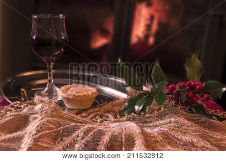 Christmas food, wine and decorations on a silver platter in front of a roaring log fire