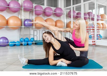 Mature female fitness instructor helping her female client during stretching workout at the gym.Professional fitness coach working at the gym assisting her client beauty recreation sportive lifestyle