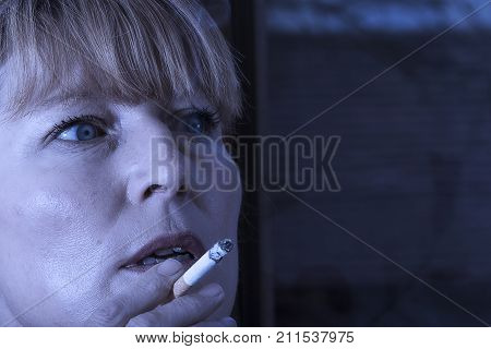 Mature adult woman smoking a tobacco cigarette indoors