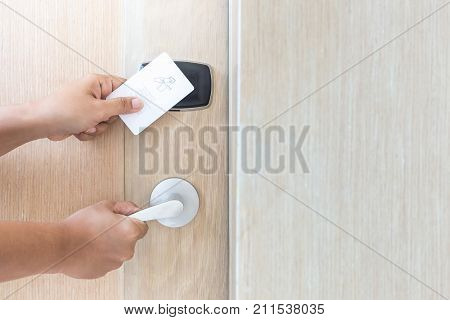 Close up hand holding white hotel key card in front of electric door