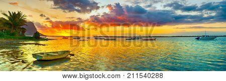 Fishing boat at sunset time. Le Morn Brabant on background. Mauritius. Panorama landscape