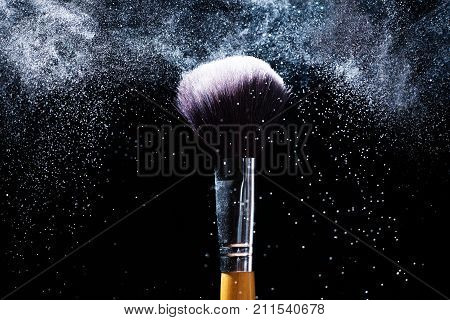Beauty and makeup concept. Cosmetics brush releasing a cloud of pink sparkling face powder over black background.