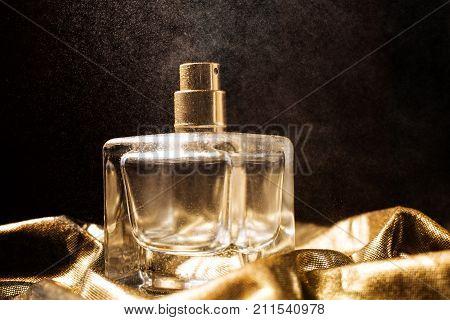 stylish bottle of wet perfume over black