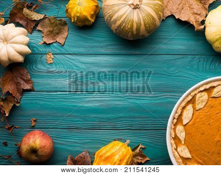 Autumn fall still life background on dark green wooden table. Pumpkins, leaves, traditional thanksgiving pumpkin pie