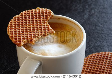 Detail Of White Mug With Milky Frothy Coffee Partially Drunk And A Partially Eaten Waffle Biscuit On