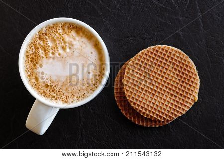 Milky Frothy Coffee In White Mug Next To A Couple Of Round Waffle Biscuits Isolated On Black Leather