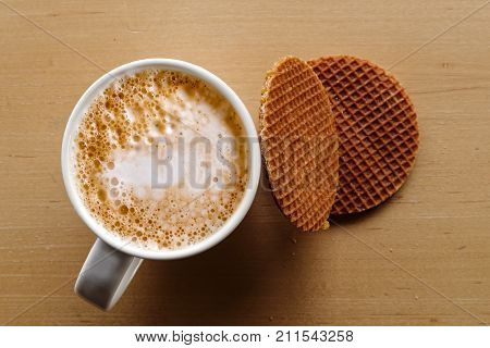 Milky Frothy Coffee In White Mug Next To A Couple Of Round Waffle Biscuits Isolated On Light Wood Fr
