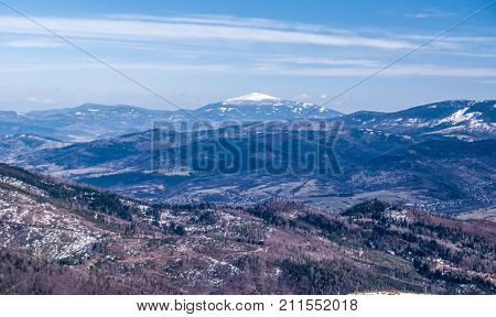 view to Babia Gora hill with lowest hills around in Zywiec Beskids mountains from Barania Gora hill in Silesian mountains in Poland during nice late winter day with blue sky