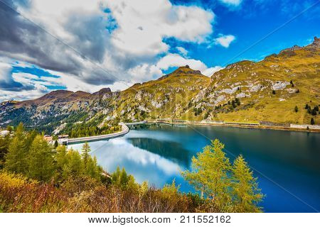 Magnificent glacial lake Lago di Fedaia in the Dolomites. The concept of ecological and extreme tourism. Cloudy cold autumn day