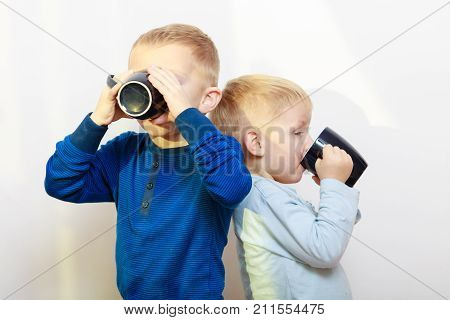 Good daily human hydration concept. Two boys thirsty kids drinking drink from black mugs