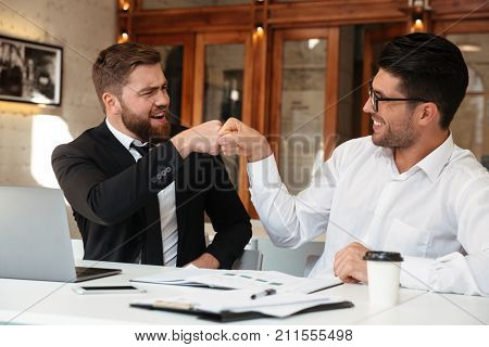 Two funny bearded colleagues in formalwear punched while sitting at office
