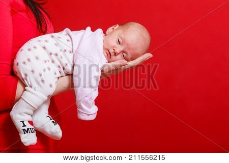 Childhood innocence concept. Little adorable newborn baby lying on mother hand. Red background.