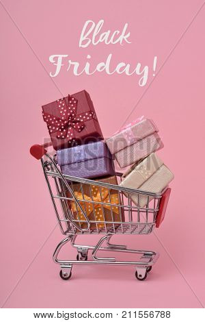 a shopping cart full of gifts of different colors and the text black friday on a pink background
