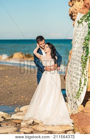 wedding copule. Beautiful bride and groom. Just merried. Close up. Happy bride and groom on their wedding hugging. Groom and Bride on the beach near the sea. wedding dress.