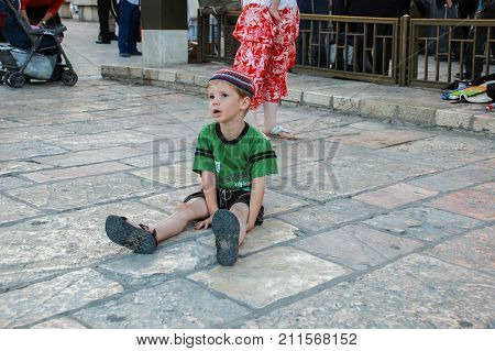 Religious Jewish Boy Sit On Stone Pavement Near To Western Wall In Jerusalem, Israel
