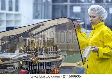 Pharmaceutical Production Worker. Pharmaceutical worker wearing protective work wear. Female worker preparing machine for work.