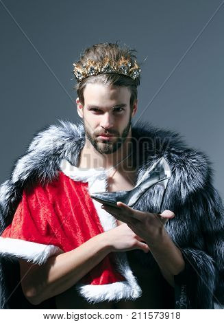 Christmas guy in santa fur coat in crown. Drag queen homosexual and trans. Cinderella prince with shoe on grey background. Freak gay and transvestite. Freedom and lgbt kitsch. poster