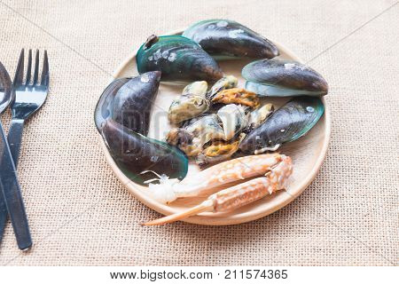Steamed mussels and crab claw on wood dish