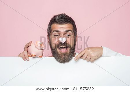 Crisis and loan. Sale and black friday shopping. Man with beard on happy face take credit. Bankruptcy and handout. Guy hold moneybox or piggy bank for savings.