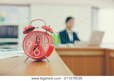 Red Alarm Clock On Office Table. Close-up Of Young Businesswoman Working On Computer In Office With