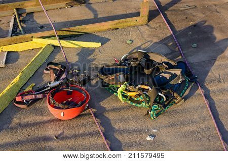 Construction worker's helmet and ropes for climbing lying on roof