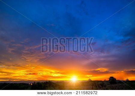 Natural Sunset Sunrise Over Field Or Meadow. Bright Dramatic Sky And Dark Ground. Countryside Landscape Under Scenic Colorful Sky At Sunset Dawn Sunrise. Sun Over Skyline Horizon. Warm Colours.