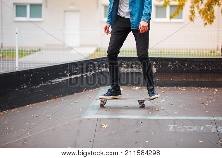 Close-up of a skateboarder's foot in an autumn skate park. A skateboarder is riding a skateboard. The concept of sport.