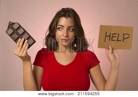 young beautiful sweet addict woman holding asking for help resisting temptation to eat chocolate bar and break diet in healthy nutrition lifestyle and weight loss concept