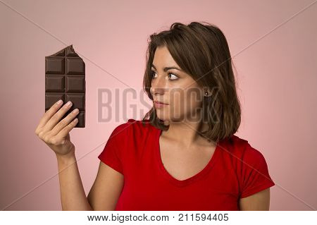 young beautiful happy and excited woman holding big chocolate bar thinking feeling temptation looking guilty skipping diet in unhealthy nutrition lifestyle and overweight sugar addiction concept