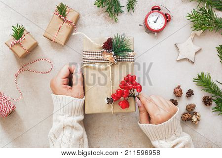 Christmas gift preparations. Woman wraps gifts for the holidays, top view, flat lay