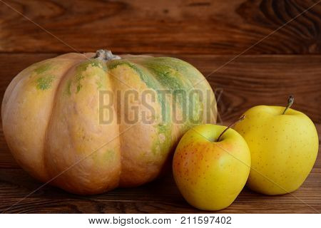 Ripe pumpkin and apples on a wooden background. Autumn harvest. Healthy eating. Closeup