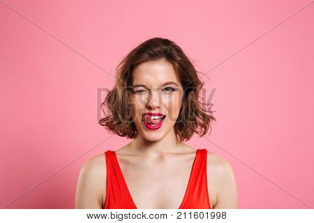 Close-up portrait of pretty playful woman winks one eye, showing tongue, looking at camera, isolated on pink background